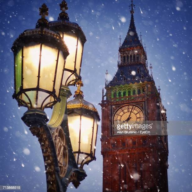 Low Angle View Of Lamp Post By Big Ben In City At Dusk During Snowfall