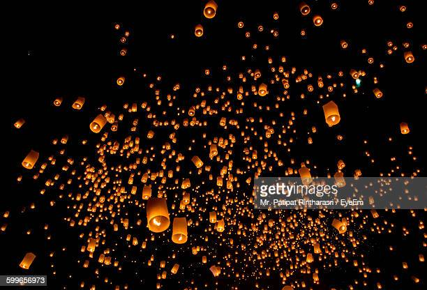 low angle view of lanterns flying against sky at night - 中国提灯 ストックフォトと画像