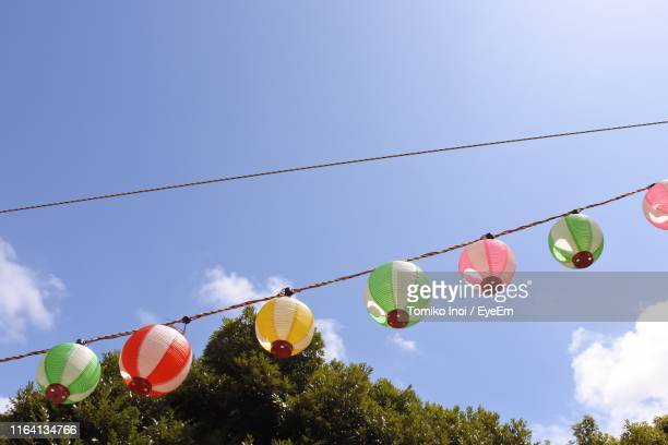 low angle view of lanterns hanging against blue sky - tomiko inoi ストックフォトと画像