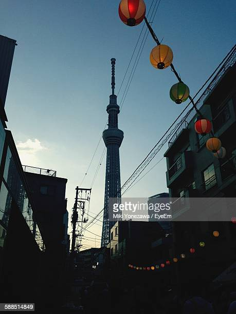 Low Angle View Of Lanterns Hanging Amidst Buildings Against Tokyo Sky Tree