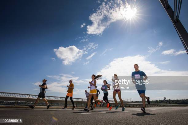 Low angle view of large group of athletic people running a marathon race on the road.