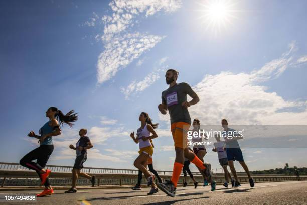 Low angle view of large group of athletic people running a marathon race on the bridge.