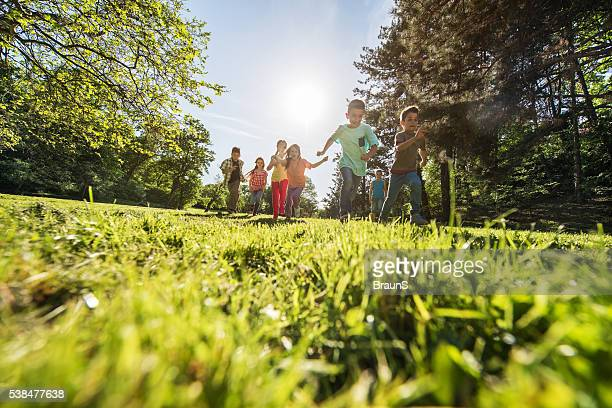 Low angle view of large group of children running outdoors.
