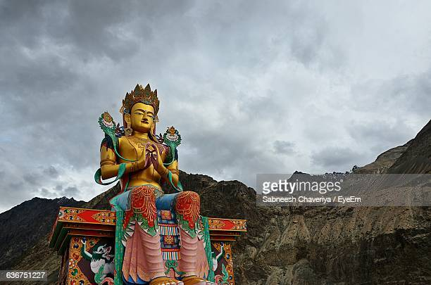 Low Angle View Of Large Maitreya Buddha Statue By Rocky Mountains Against Cloudy Sky