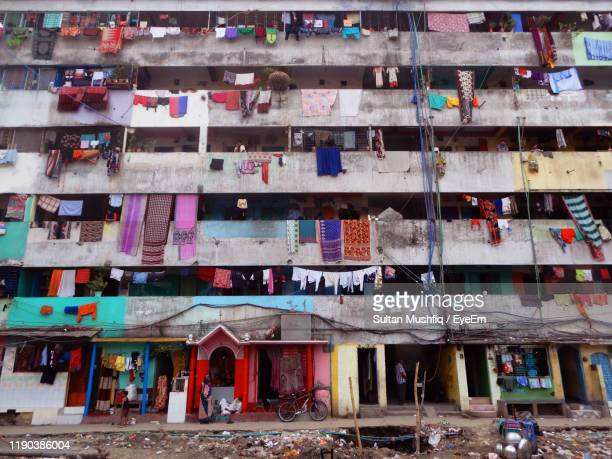 low angle view of laundry hanging in balcony of building - dhaka stock-fotos und bilder
