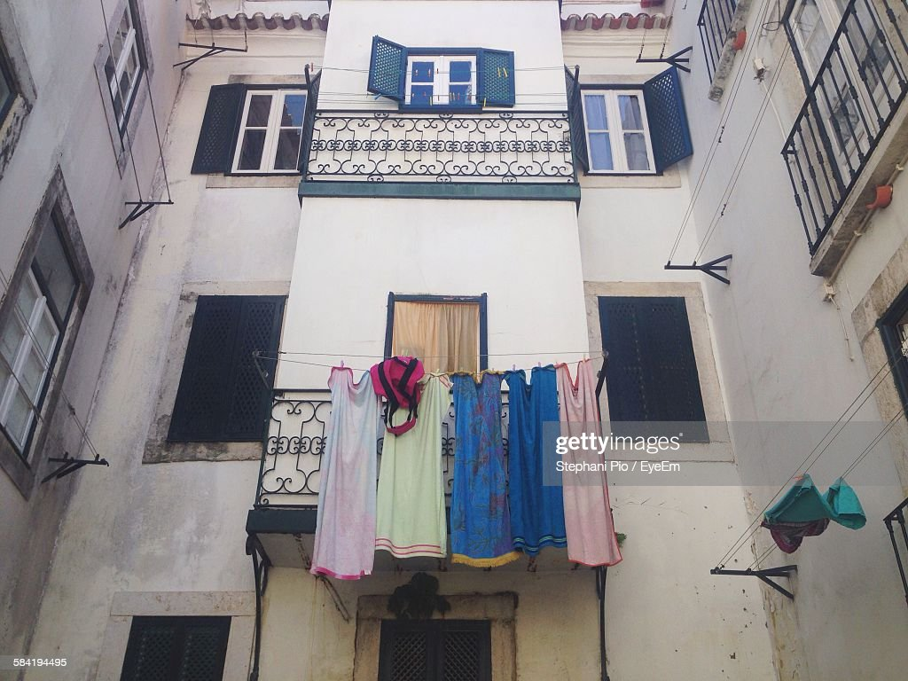 Low Angle View Of Laundry Hanging On Clothesline In Apartment Balcony Stock Photo