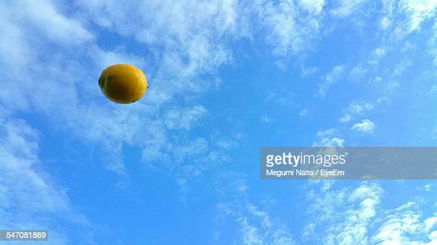 Low Angle View Of Lemon In Mid-Air Against Blue Sky