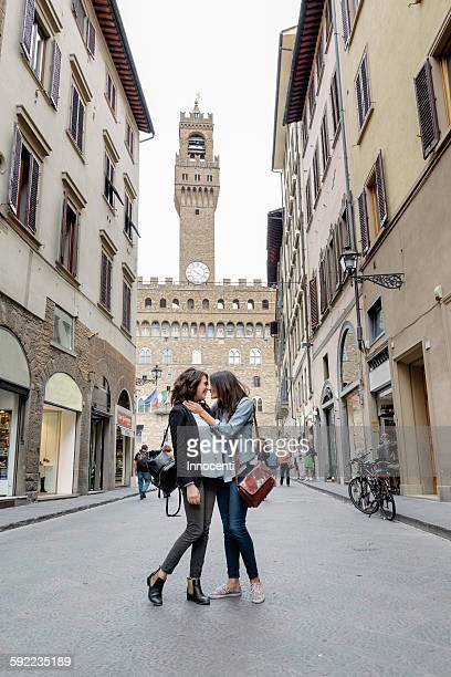 Low angle view of lesbian couple standing in street below the Palazzo Vecchio face to face hugging, Florence, Tuscany, Italy