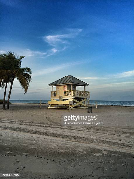 Low Angle View Of Lifeguard Hut At Beach Against Blue Sky