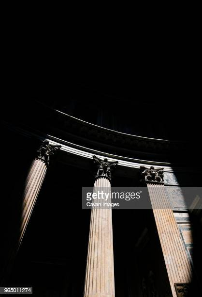 low angle view of light falling on architectural columns of pantheon during night - pantheon roma foto e immagini stock