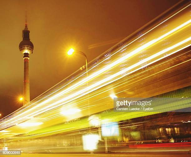 Low Angle View Of Light Trails Over Illuminated Street Against Fernsehturm Tower