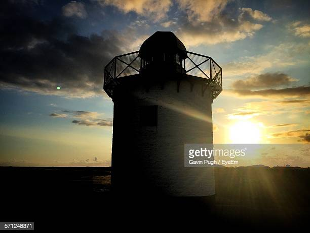 low angle view of lighthouse against cloudy sky during sunset - llanelli stock pictures, royalty-free photos & images