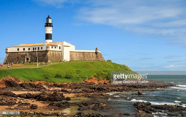 Low Angle View Of Lighthouse By Sea Against Sky On Sunny Day