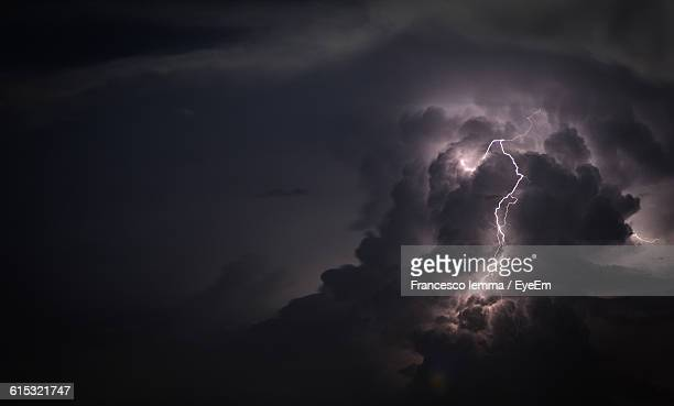 Low Angle View Of Lightning Against Cloudy Sky At Dusk