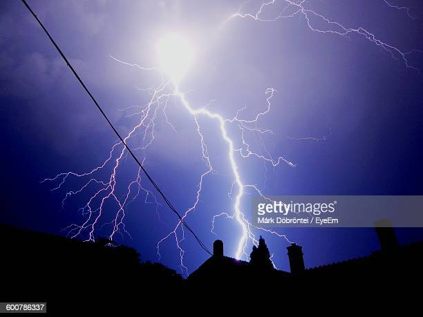 Low Angle View Of Lightning In Sky Over Silhouette Houses