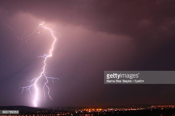 Low Angle View Of Lightning Over Illuminated Town At Night