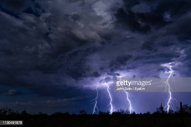 low angle view of lightning over silhouette landscape at night - sturm stock-fotos und bilder