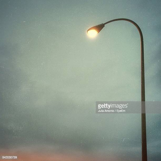 Low Angle View Of Lit Street Light Against Cloudy Sky