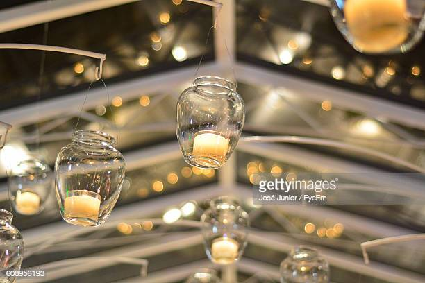 Low Angle View Of Lit Tea Light Candles Hanging Indoors