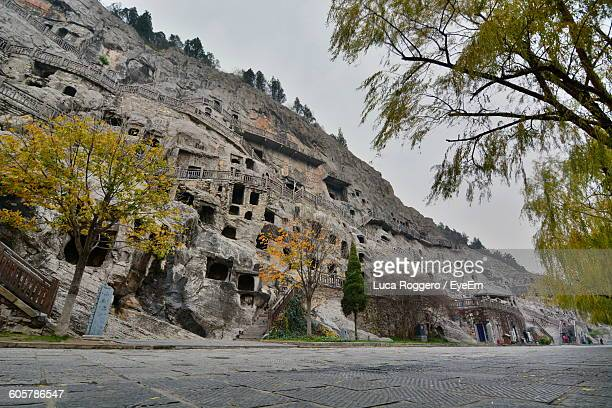 low angle view of longmen grottoes against sky - henan province stock photos and pictures