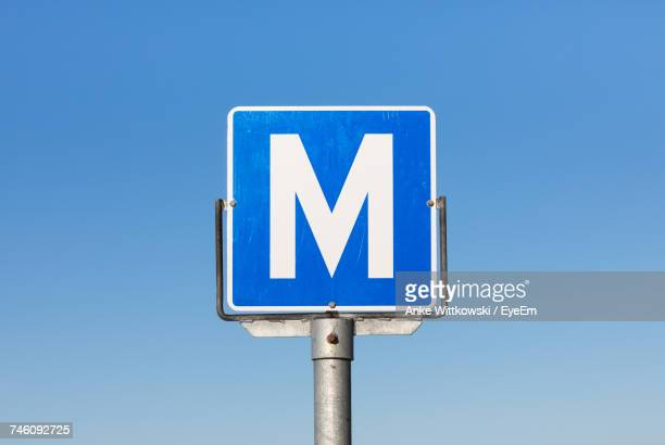 low angle view of m sign against clear blue sky - letter m stock pictures, royalty-free photos & images