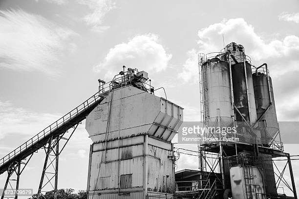 Low Angle View Of Machinery At Cement Factory Against Sky
