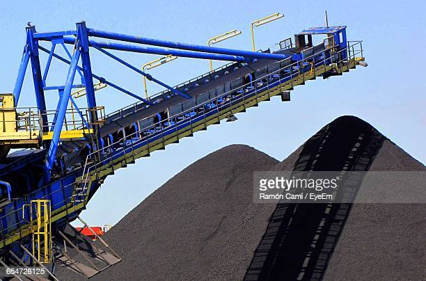 Low Angle View Of Machinery By Coal Heap At Industry