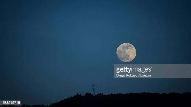 Low Angle View Of Majestic Moon On Silhouette Field