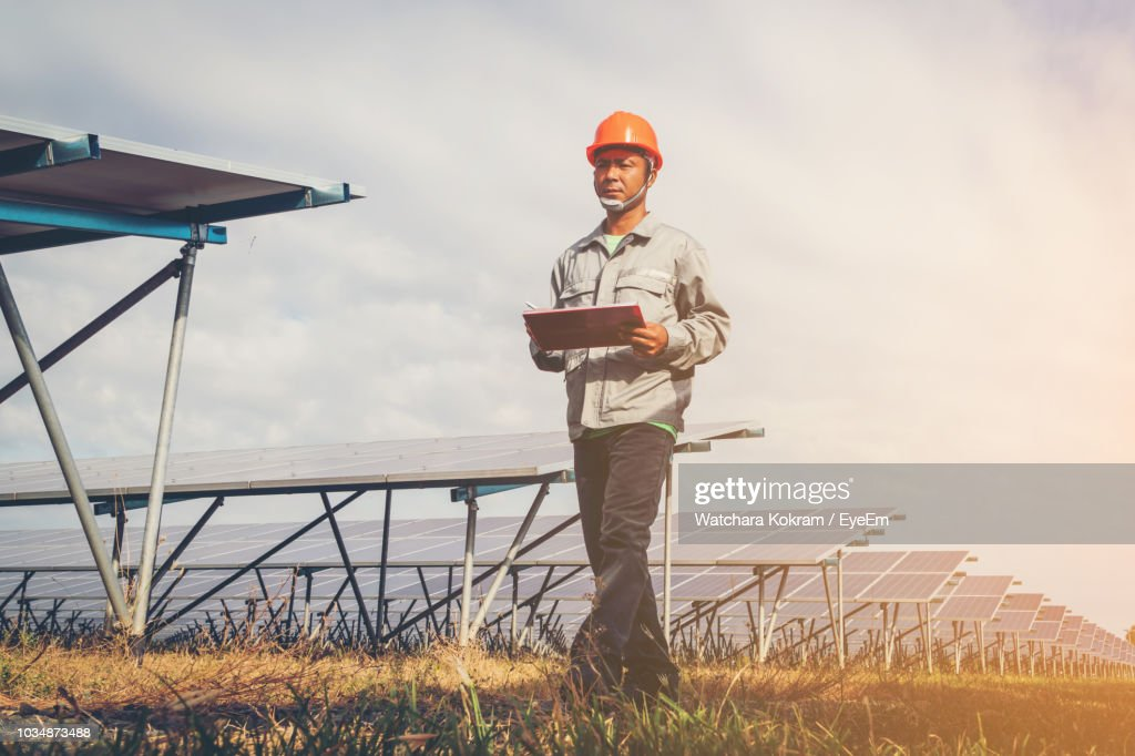 Low Angle View Of Male Electrician Walking Against Solar Panels On Field : Stock Photo