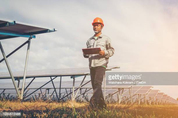 low angle view of male electrician walking against solar panels on field - power occupation stock photos and pictures