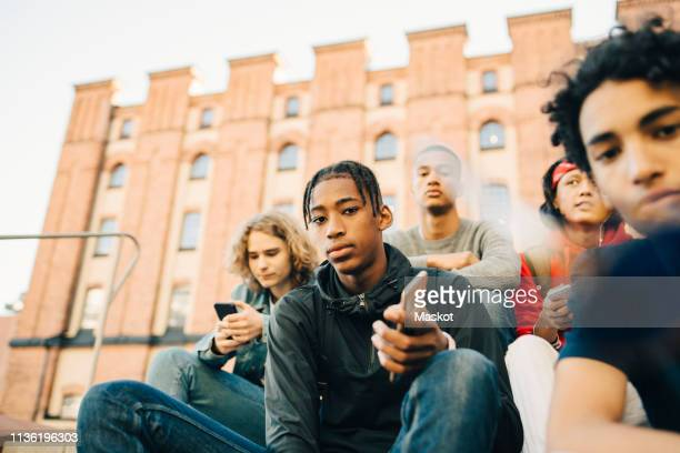 low angle view of male friends sitting in city - cinq personnes photos et images de collection