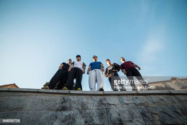 low angle view of male friends standing on retaining wall against sky - 5人 ストックフォトと画像
