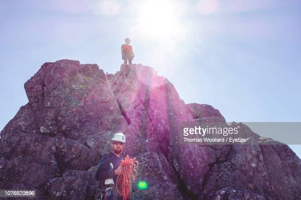 Low Angle View Of Male Hikers Hiking On Mountain Against Clear Sky