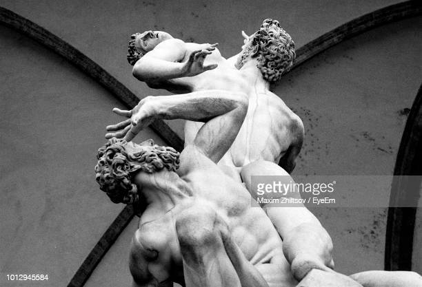 low angle view of male statues against wall - sculptuur stockfoto's en -beelden