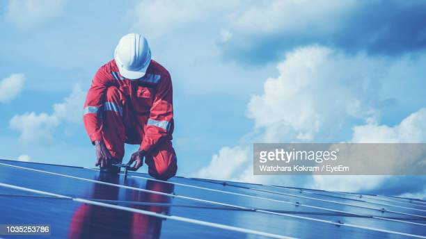 Low Angle View Of Male Technician Repairing Solar Panels Against Cloudy Sky
