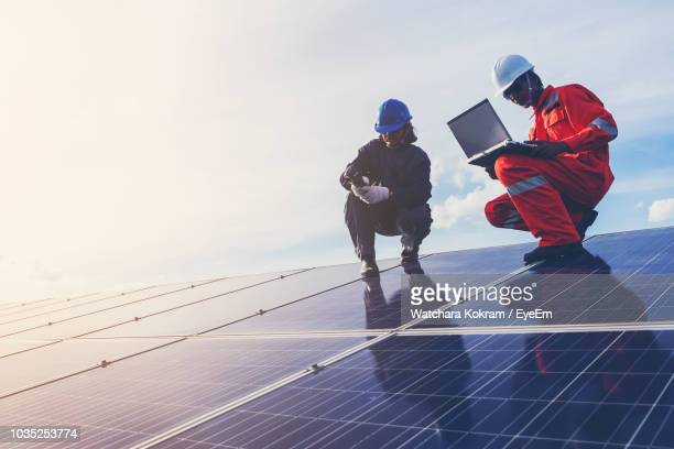 low angle view of male technicians working on solar panels against sky - contact list stock photos and pictures
