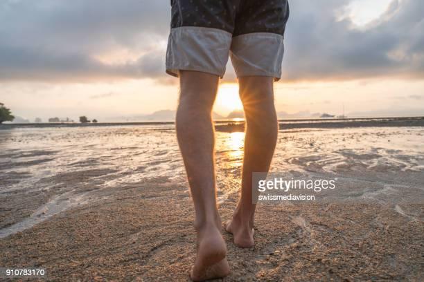 日の出のビーチで歩く男性の低角度表示