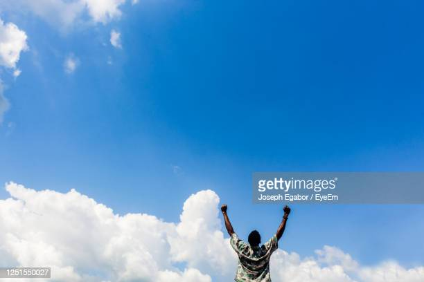 low angle view of man against blue sky - spirituality stock pictures, royalty-free photos & images