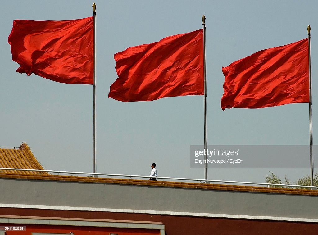 Low Angle View Of Man And Red Flags On Building Against Sky : Stock Photo
