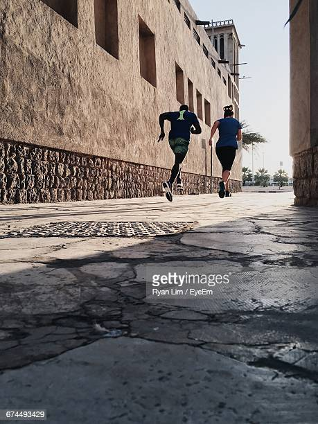 Low Angle View Of Man And Woman Jogging On Pathway During Sunny Day