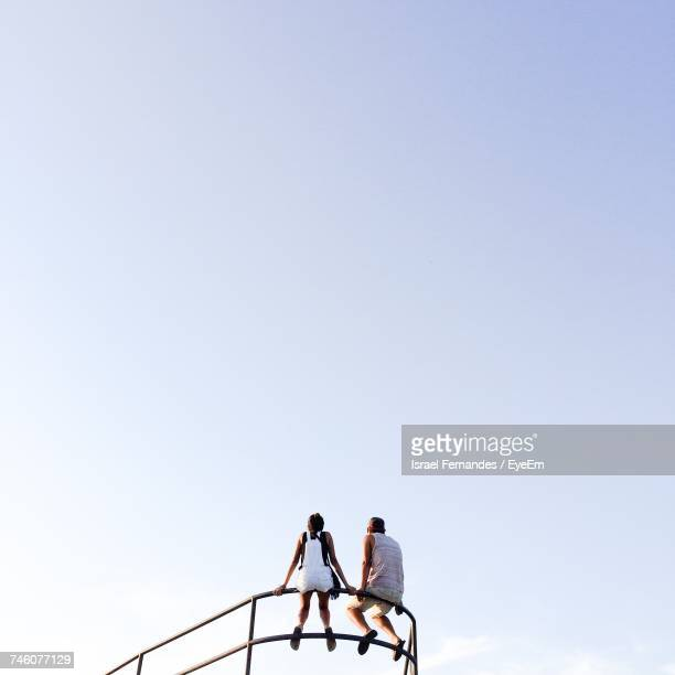 low angle view of man and woman sitting against clear sky on sunny day - taken on mobile device stock photos and pictures