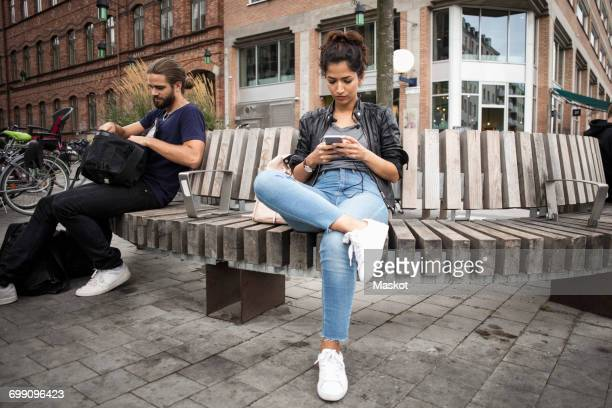 Low angle view of man and woman sitting on wooden bench against building in city