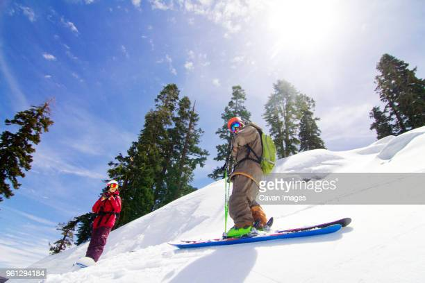 Low angle view of man and woman standing on snowcapped mountain against sky
