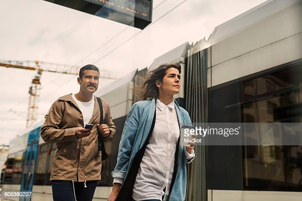 Low angle view of man and woman walking by tram at station