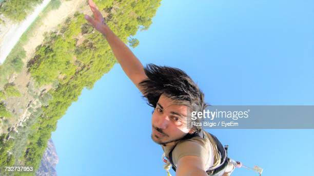 Low Angle View Of Man Bungee Jumping Against Blue Sky