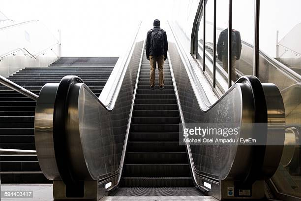 Low Angle View Of Man Carrying Backpack Standing On Escalator