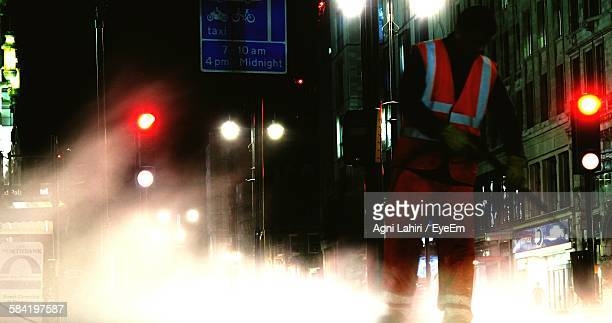 low angle view of man cleaning illuminated street at night - street sweeper stock pictures, royalty-free photos & images