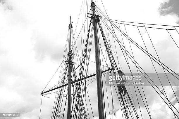 Low Angle View Of Man Climbing Mast Of Sailboat