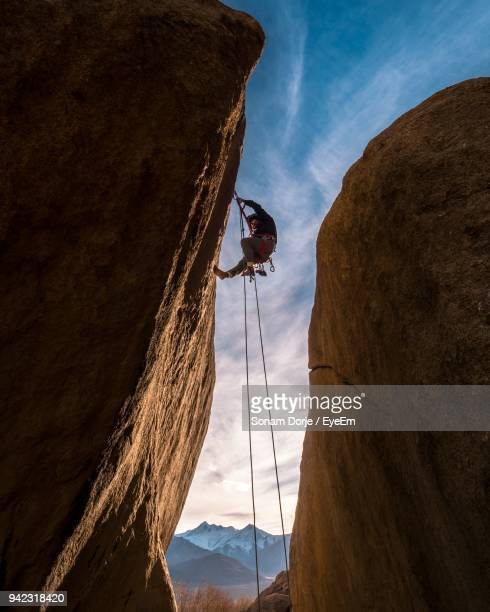 low angle view of man climbing on rock against sky - rock climbing stock pictures, royalty-free photos & images
