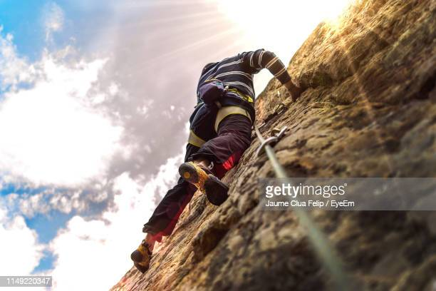low angle view of man climbing on rock formation - rock climbing stock pictures, royalty-free photos & images
